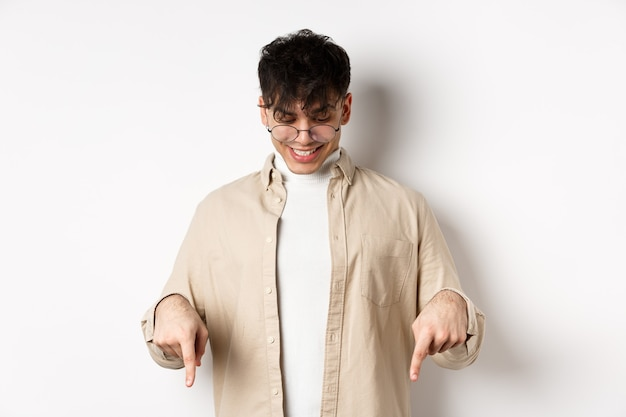 Stylowy, nowoczesny facet w okularach wskazujących, patrzący w dół ze szczęśliwym uśmiechem, pokazujący transparent, stojący na białym tle