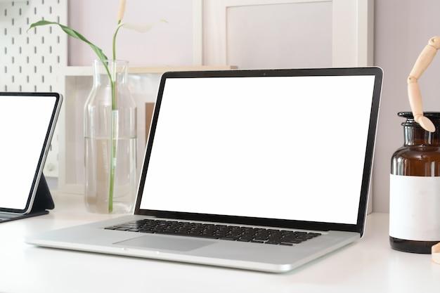 Stylowy obszar roboczy z pustym ekranem laptopa i materiałów biurowych