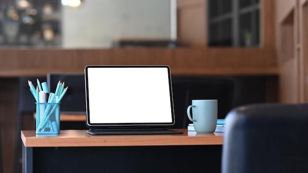 Stylowy obszar roboczy z tabletem komputerowym, papeterią i filiżanką kawy na drewnianym stole