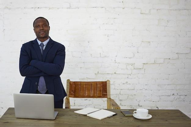 Stylowy, odnoszący sukcesy afrykańsko-amerykański przedsiębiorca mężczyzna pewnie patrzy na swoje miejsce pracy przed białym murem z miejscem na tekst lub informacje promocyjne