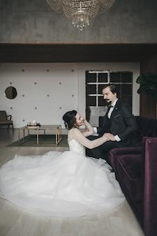 Stylowy pan młody i piękna panna młoda w białej sukni siedzi na poddaszu. portret ślubny nowożeńców szczęśliwy i uśmiechnięty.