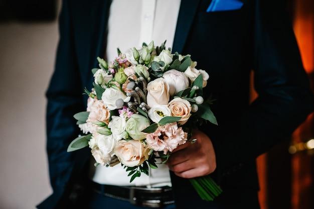 Stylowy pan młody trzyma bukiet ślubny. bukiet ślubny w rękach człowieka.