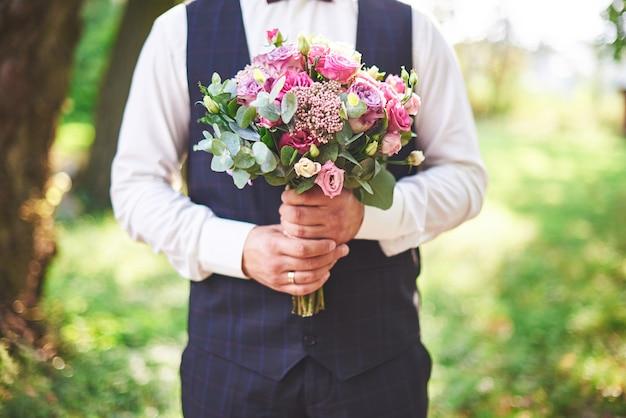 Stylowy pan młody trzyma delikatny różowy bukiet ślubny.