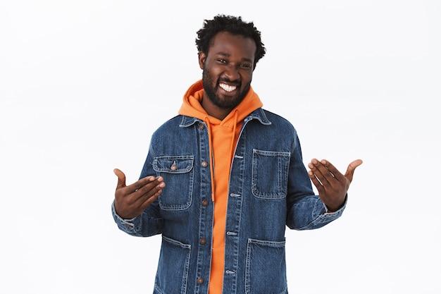 Stylowy, pewny siebie, przystojny afroamerykanin w dżinsowej kurtce, pomarańczowej bluzie z kapturem, wpadającym w klimat jesiennych wakacji