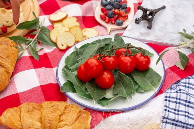 Stylowy piknik na zielonym trawniku. świeże rogaliki i czajniczek z herbatą na narzutę w pobliżu wiklinowego żeńskiego kapelusza. treść na instagramie