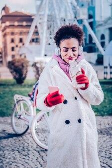 Stylowy płaszcz. ładna młoda kobieta ubrana w stylowy płaszcz, spędzając wolny czas na świeżym powietrzu