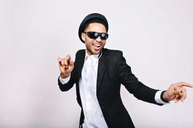 Stylowy podekscytowany facet w garniturze, kapeluszu, czarnych okularach przeciwsłonecznych, dobrze się bawi. wypoczynek, weekendy, wesoły nastrój, radość, szczęście, tancerz, śpiew, nowoczesny biznesmen, odizolowany.