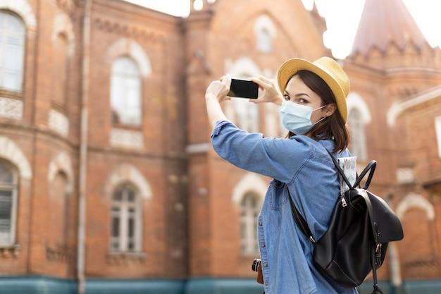 Stylowy podróżnik z kapeluszem fotografujący na wakacjach
