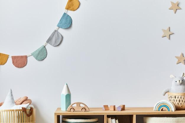 Stylowy pokój dla noworodka skandynawskiego z zabawkami, pluszowym zwierzakiem, aparatem fotograficznym i akcesoriami dla dzieci. przytulna ozdoba i wiszące waciki na białej ścianie. skopiuj miejsce.