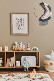 Stylowy pokój dla noworodka w stylu skandynawskim z brązową drewnianą ramą plakatową, zabawkami, pluszowymi zwierzętami i akcesoriami dziecięcymi. przytulna dekoracja i wiszące bawełniane flagi na beżowej ścianie.