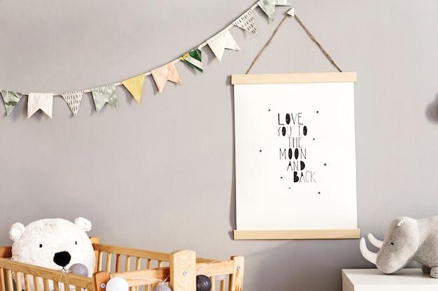 Stylowy pokój dziecięcy scandi z drewnianą ramką na zdjęcia, drewnianymi i pluszowymi zabawkami, pudełkami, klockami i akcesoriami. wzór gwiazdek na ścianie w tle. jasne i słoneczne wnętrze. wystrój domu.