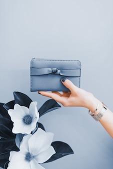 Stylowy portfel damski w rękach dziewczynki z ciemnoniebieskim manicure. kolor roku 2020.
