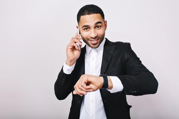 Stylowy portret elegancki młody człowiek w białej koszuli i czarnej kurtce rozmawia przez telefon, pokazuje zegarek i uśmiecha się. biznesmen, praca, spotkanie, wesoły nastrój, uśmiech