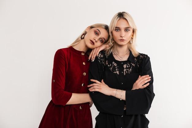 Stylowy portret młode atrakcyjne blondynki siostry kobiety w czerwonych i czarnych modnych sukienkach w pobliżu białej ściany vintage