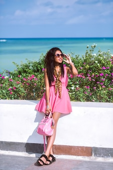 Stylowy portret mody ładnej młodej tajskiej azjatki pozującej w pobliżu plaży w luksusowym hotelu i ciesz się wakacjami, modną różową sukienką, szalikiem w lamparta i okularami przeciwsłonecznymi, podróżnym nastrojem.