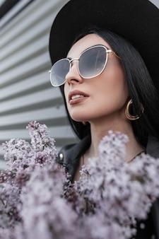 Stylowy portret pięknej kobiety z seksownymi ustami w modnych okularach przeciwsłonecznych w skórzanej kurtce w czarnym eleganckim kapeluszu z pięknym bukietem kwiatów bzu w pobliżu zabytkowej metalowej ściany w mieście. urocza dziewczyna się cieszy
