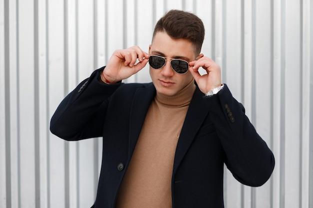 Stylowy, poważny młody hipster mężczyzna w stylowych okularach przeciwsłonecznych w beżowym swetrze z dzianiny w modnej kurtce pozuje i patrzy w kamerę na ulicy w pobliżu srebrnej ściany