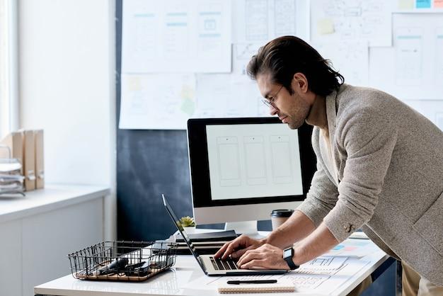 Stylowy pracownik biurowy za pomocą laptopa