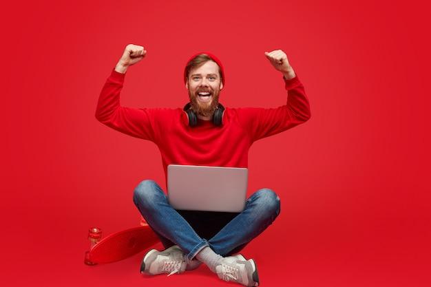 Stylowy programista z laptopem świętującym sukces