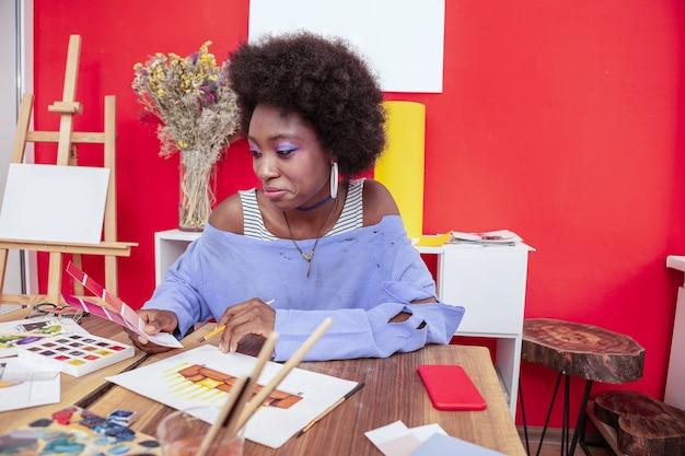 Stylowy projektant. stylowy projektant wnętrz w niebieskiej koszuli z otwartymi ramionami, który wybiera kolor