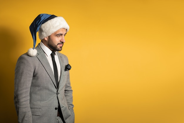Stylowy przemyślany przystojny mężczyzna ubrany w niebieski kapelusz świętego mikołaja i garnitur, patrząc z przodu na białym tle na żółtej ścianie