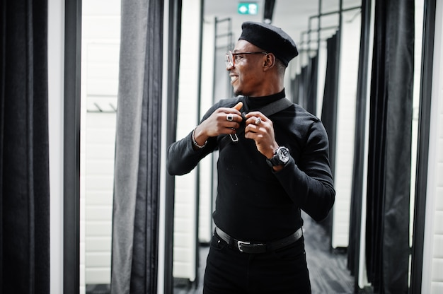 Stylowy przypadkowy mężczyzna w stroju i berecie z torbą w talii w sklepie z przymierzalniami, patrząc w lustro.