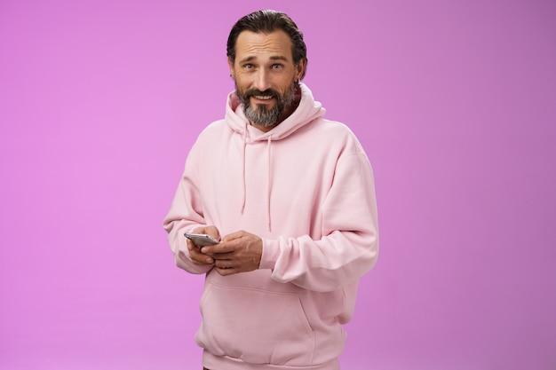 Stylowy, przystojny, dorosły, brodaty facet w wieku 40 lat w modnej różowej bluzie z kapturem, trzymający smartfon i wysyłający sms-y wygląd aparatu, niezachwiany fajny, pewny siebie rozproszony, grając w niesamowitą nową grę z aplikacjami, fioletowe tło.