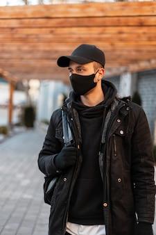 Stylowy przystojny mężczyzna w masce ochronnej w modnych ubraniach z kurtką, bluzą z kapturem, czapką makiety i plecakiem spaceruje po mieście. miejski styl odzieży męskiej