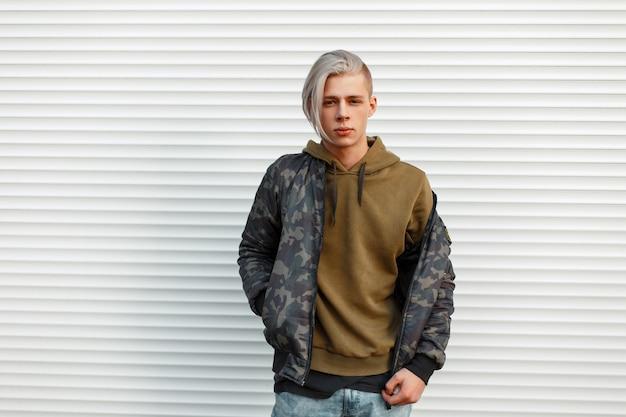 Stylowy przystojny mężczyzna w modnej wojskowej kurtce z kapturem pozuje w pobliżu białej metalowej ściany
