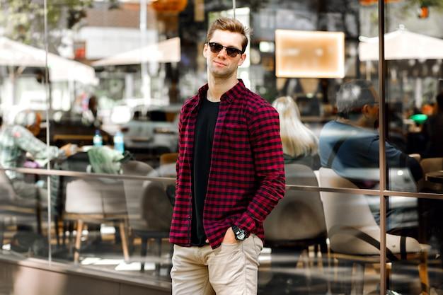 Stylowy przystojny młody biznesmen siedzi na ulicy, niesamowity uśmiech, brązowe włosy i oczy, ubrany w koszulę w kratę hipster i beżowe spodnie, okulary przeciwsłoneczne i zegarki, pozuje w pobliżu restauracji.
