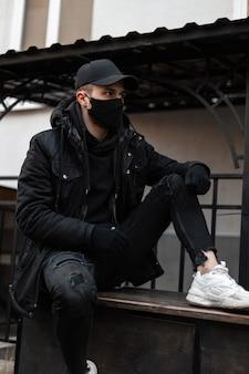 Stylowy przystojny młody facet z medyczną maską ochronną i czarną czapką w modnych ubraniach z kurtką i bluzą z kapturem na ulicy. miejska moda i styl pandemii dla mężczyzn