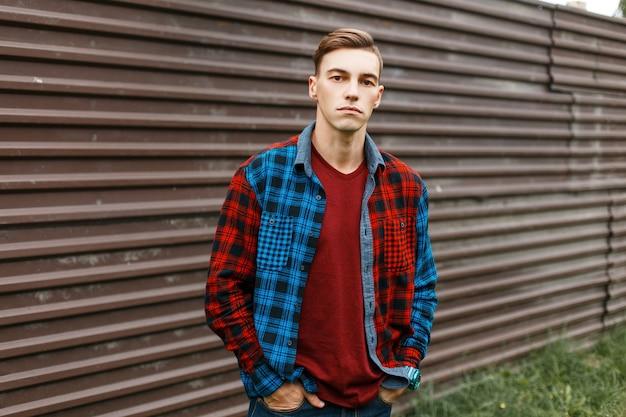 Stylowy przystojny młody mężczyzna w modnej czerwonej koszulce w modnej kraciastej wielobarwnej koszuli w dżinsach na zewnątrz w pobliżu metalowego ogrodzenia w stylu vintage. atrakcyjny amerykanin lubi spacerować.