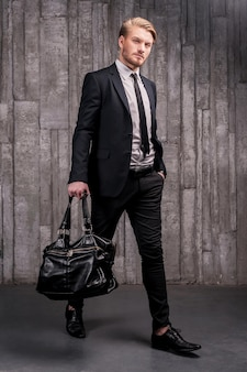 Stylowy przystojny. pełna długość przystojnego młodego mężczyzny w formalnej odzieży, niosącego czarną torbę