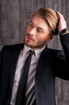Stylowy przystojny. przystojny młody mężczyzna w formalnym stroju dotyka włosów ręką i odwraca wzrok