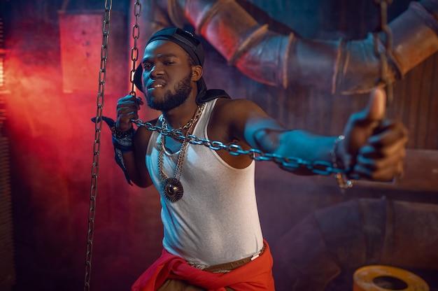Stylowy raper pozuje z łańcuchami w studio z fajnymi podziemnymi dekoracjami. wykonawca hip-hopu, piosenkarz rapu, break dance