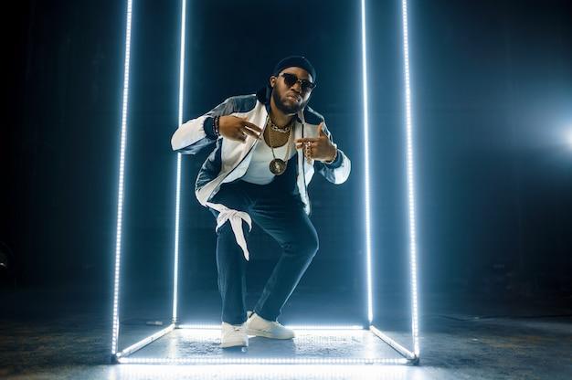 Stylowy raper w złotej biżuterii i okularach przeciwsłonecznych, wykonawca hip-hopu z ciemnymi ścianami, piosenkarz rapu, występy break dance, rozrywkowy styl życia