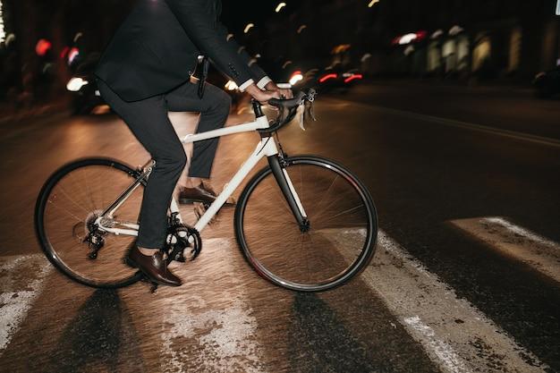 Stylowy rowerzysta przejazd przez ulicę w mieście w nocy