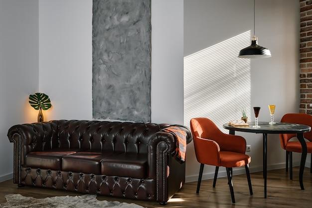 Stylowy salon i jadalnia w stylu loftu z hebanowym stołem i czerwonymi fotelami