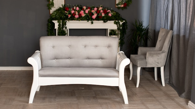 Stylowy salon z wygodną szarą narożną sofą, małym drzewem na podłodze i czarnym zegarem na ciemnej ścianie