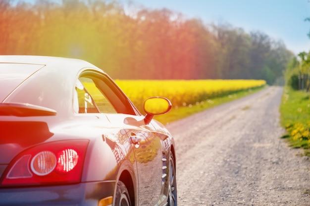 Stylowy samochód sportowy na wiejskiej drodze w słoneczny dzień