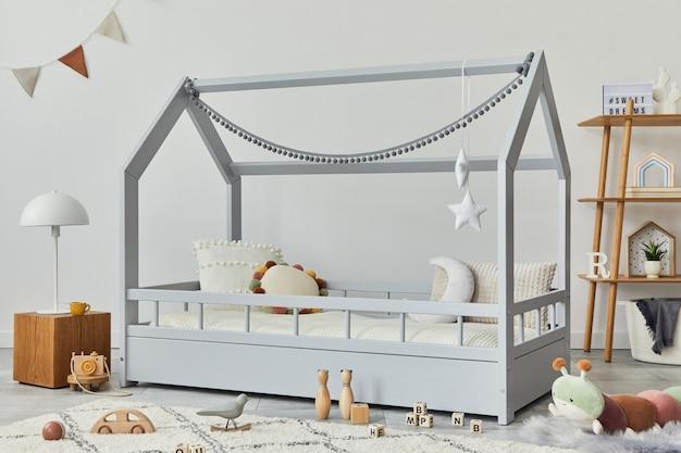 Stylowy skandynawski pokój dziecięcy z kreatywnym drewnianym łóżkiem, drewnianą kostką, lampą, drewnianą półką, pluszowymi i drewnianymi zabawkami oraz wiszącymi tekstylnymi dekoracjami. szare ściany, dywan na podłodze. szablon.