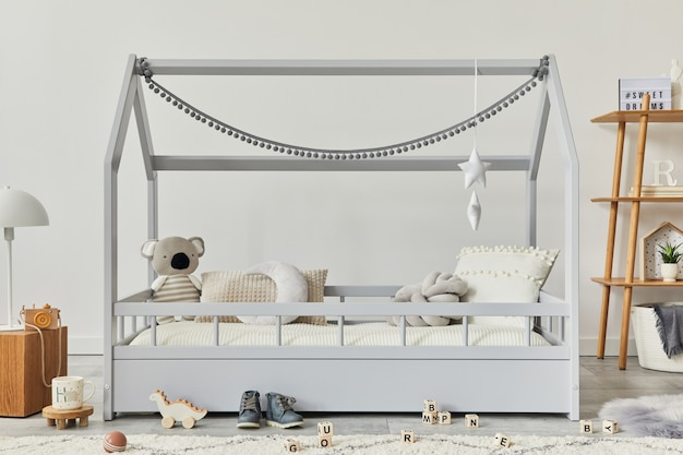 Stylowy skandynawski pokój dziecięcy z kreatywnym drewnianym łóżkiem, drewnianą kostką, lampą, drewnianą półką, pluszowymi i drewnianymi zabawkami oraz wiszącymi tekstylnymi dekoracjami. szare ściany. szablon.