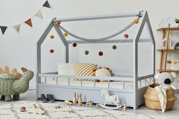 Stylowy skandynawski pokój dziecięcy z kreatywnym drewnianym łóżkiem, poduszkami, drewnianą półką, pluszowymi i drewnianymi zabawkami oraz wiszącymi tekstylnymi dekoracjami. szare ściany, dywan na podłodze. szablon.