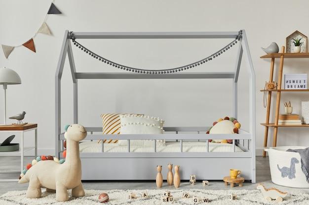 Stylowy skandynawski pokój dziecięcy z kreatywnym drewnianym łóżkiem, stolikiem kawowym, lampą, drewnianą półką, pluszowymi i drewnianymi zabawkami oraz wiszącymi tekstylnymi dekoracjami. szare ściany, dywan na podłodze. szablon.