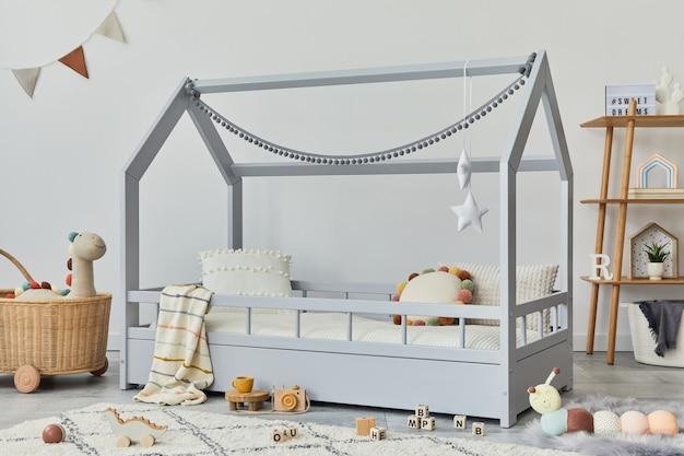 Stylowy skandynawski pokój dziecka z kreatywnym drewnianym łóżkiem, rattanowym koszem, drewnianą półką, pluszowymi i drewnianymi zabawkami oraz wiszącymi tekstylnymi dekoracjami. szare ściany, dywan na podłodze. szablon.