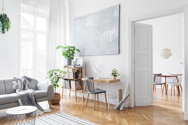 Stylowy skandynawski salon z designerskimi meblami, roślinami, bambusowym regałem, drewnianym biurkiem, obrazami artystycznymi, brązowym parkietem w nowoczesnym wystroju domu