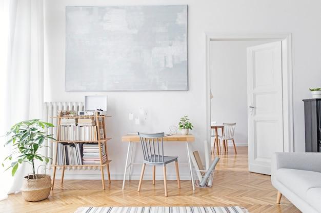 Stylowy skandynawski salon z kreatywnym drewnianym biurkiem, szarą sofą, bambusowym regałem, książkami, roślinami i eleganckimi dekoracjami w designerskim wystroju domu