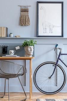 Stylowy skandynawski salon z ramą plakatową na półce, drewnianym biurkiem, rowerem, artykułami biurowymi i osobistymi akcesoriami w projektowym wystroju domu
