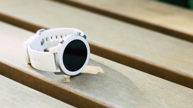 Stylowy smartwatch. zbliżenie na nowy, nowoczesny, biały smartwatch z czarnym okrągłym ekranem leżącym na drewnianej łące.