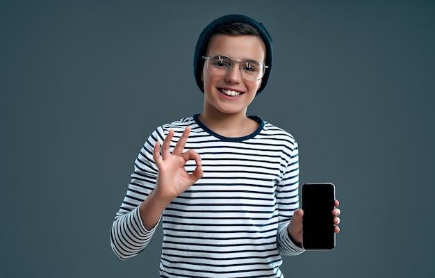 Stylowy sprytny uczeń w kapeluszu i okularach ze smartfonem pokazuje ok gest na białym tle na szarym tle.